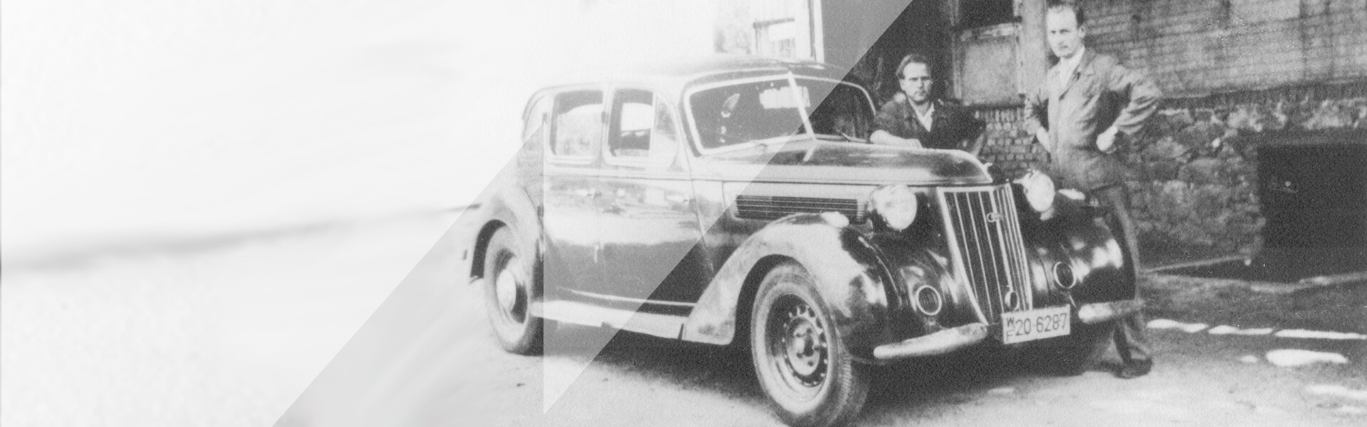 old picture in black and white showing a car and two men