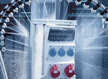 An AMAXX® receptacle combination by MENNEKES is sprayed with water in the test laboratory.