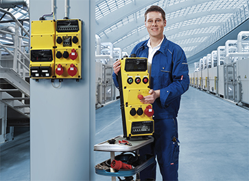 A man in blue overall is holding a yellow AMAXX® receptacle combination by MENNEKES in his hand. In addition, a yellow AMAXX® is mounted on the wall directly next to him.
