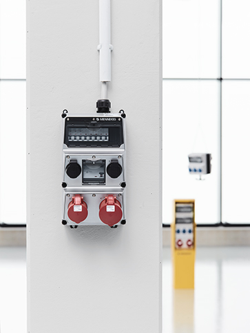 A wall mounted receptacle combination by MENNEKES in the foreground. A free-standing, a mobile and a suspendable receptacle combination by MENNEKES are shown in the background.